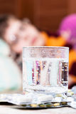 Glass with dissolved medicament in and pills. On table close up and sick woman with scarf around her neck on sofa in living room on background Royalty Free Stock Photo