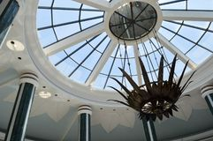 Glass dome, the roof of a building with many windows and beautiful columns, with a chandelier against a blue sky. A glass dome, the roof of a building with many stock photos