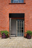 Glass door in brick wall with two flowerpots Stock Photography