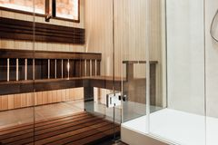 Glass door design in the sauna and shower cabin with metal door hinge. In the interior royalty free stock image