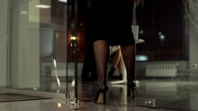 A glass door opens, women`s shoes enter the office.