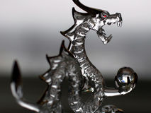 Glass Dragon. Close up of glass dragon. Focus from soft to sharp emphasizing the dragons head and crystal ball royalty free stock photos