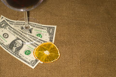 Glass, a dried orange slice and a few bills on the tablecloth Royalty Free Stock Photography