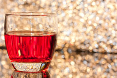 Glass with drink. On bokeh background Royalty Free Stock Photography