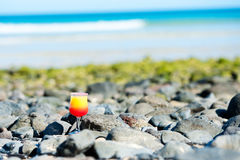 A glass with drink on the beach by the sea Stock Photography