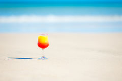 A glass with drink on the beach by the sea Stock Photos