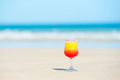 A glass with drink on the beach by the sea Royalty Free Stock Image