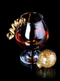 Glass with drink and a Christmas ball. Stock Photo