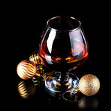 Glass with drink and a Christmas balls. Royalty Free Stock Image