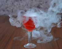 Glass, drink, cocktail, alcohol, red, wine, beverage, martini, isolated, liquid, fruit, dessert, white, cold, food, ice, strawberr. Crystal glass with smoke Stock Photo