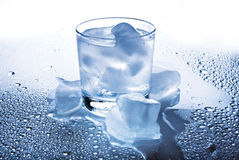 Glass with a drink and ice Stock Photos