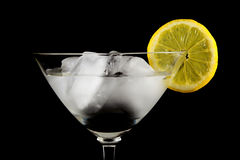 Glass of drink with ice and lemon closeup isolated on a black Royalty Free Stock Images