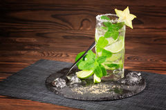 A glass of drink from lime, rum, mint, decorative carambola and crushed ice on a wooden background. Summer mojito. Copy space. Royalty Free Stock Images