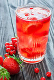 Glass of drink with strawberry and red currant berries on wooden Stock Photos