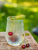 Glass with drops of dew and cherries Royalty Free Stock Photo