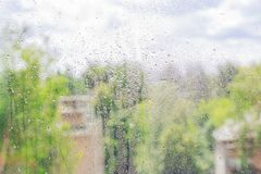 The glass in drops of rain. The view from the window of the city. Rainy day. Autumn mood stock photo