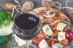 A glass of dry red wine and Italian Focaccia bread with cheese and a cheese platter with figs and Gorgonzola, brie, DorBlu and gra Stock Images