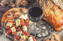 A glass of dry red wine and Italian Focaccia bread with cheese and a cheese platter with figs and Gorgonzola, brie Stock Photo