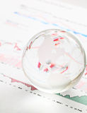 Glass earth ball on the financial chart Stock Photos