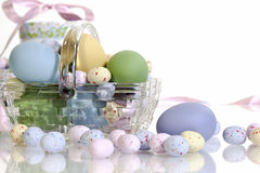 Glass Easter Basket. A glass Easter basket filled with colored and candy eggs on white background Stock Image