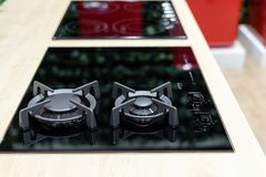 Glass electric-gas hob in modern kitchen interior. Combined or mix energy types of stove concept. Built-in black glass electric-gas hob in modern kitchen stock images