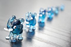 Glass elephants. Six blue glass elephants on wooden background Royalty Free Stock Image
