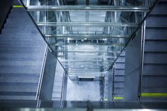 Glass elevator, concrete staircase. Glass elevator shaft and concrete staircase leading down towards an underground train station in Vienna, Austria Royalty Free Stock Photo