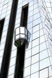 Glass elevator at the exterior Stock Photos