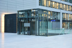 Glass Elevator in Frankfurt airport. Glass elevator for transporting people at the airport. In the background there is a glass building with business offices Royalty Free Stock Photography