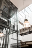 Glass elevator in modern building. Closeup of a glass elevator in modern spacious building of university Stock Photos