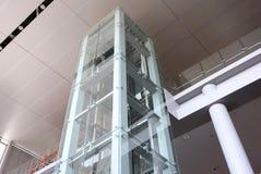 Glass elevator. Glass tubular elevator in modern building Stock Images