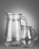 Glass, empty jugs. On sport gray background Stock Photography