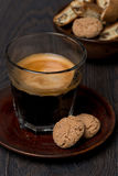 Glass of espresso and almond cookies on dark background, closeup Royalty Free Stock Images