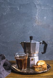 Glass espresso coffee on rustic wooden board, cantucci biscuits and steel Italian Moka pot, grey background Stock Photos