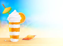 Glass of exotic orange cocktail on beach Royalty Free Stock Images