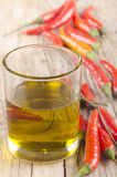 Glass with extra virgin olive oil. And chili on a wooden table Stock Images