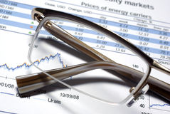 Glass of eyewear and financial report. Glass of eyewear and financial report macro Royalty Free Stock Image