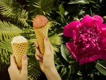 Glass för flickahållfrukt nära ormbunke och pionen blommar royaltyfri foto