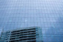 Glass facade of Aldgate Tower in Whitechapel High Street, London, with reflection of the sky and the building opposite stock photography