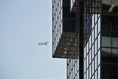 Glass facade detail of modern building  and airplane on the sky in the background. The glass facade detail of modern building  and airplane on the sky in the Royalty Free Stock Photos