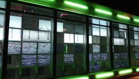 Glass facade with green Turquoise blue reflections of wind energy wheels royalty free stock photography