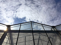 Glass facade of industrial greenhouse against cloudy sky Stock Images