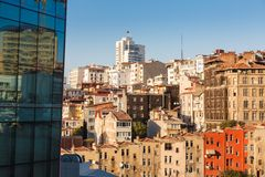 Glass facade of a modern building and old houses. Glass facade of a modern building and direct row of old colored houses in Istanbul on background blue sky Royalty Free Stock Photo