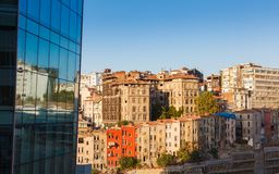 Glass facade of a modern building and old houses. Glass facade of a modern building and direct row of old colored houses in Istanbul on background blue sky Royalty Free Stock Images