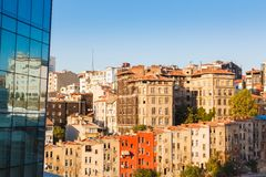 Glass facade of a modern building and old houses. Glass facade of a modern building and direct row of old colored houses in Istanbul on background blue sky Stock Photos