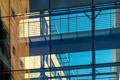 Glass facade of a modern building - orange and blue. Glass facade modern building orange blue royalty free stock images