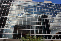Glass facade of a modern office building with reflections of the cloudy sky. Stock Image