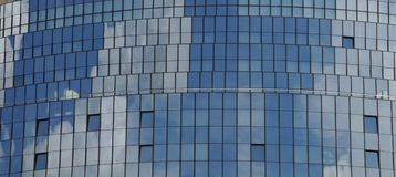 Glass facade reflecting cloudy sky. Curved facade of a modern building reflecting blue sky with white clouds Royalty Free Stock Photography