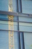 Glass facade reflecting construction crane. Shuttered glass facade of a modern office building reflecting lattice steel construction of a crane Royalty Free Stock Image