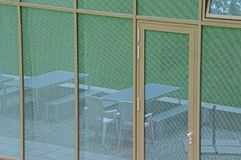 Glass facade reflecting garden furniture. Glass facade of an office building with windows and door reflecting tables and seat on terrace and lawn behind garden Royalty Free Stock Images